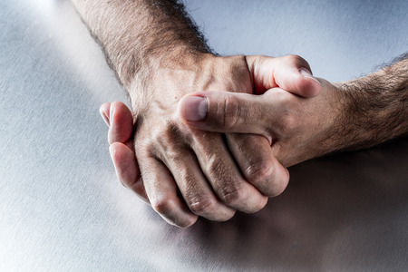 embarrassment: anonymous male hairy hands comforting each against anxiety, tension, embarrassment or impatience communicating about nervous body language and hand gesture