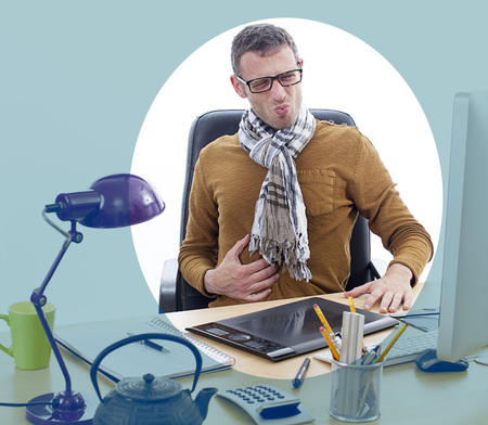 sick middle aged male entrepreneur or independent man suffering from painful stomach ache at his office desk with teapot and business notes for stress and body tension, focus blue effect Stock Photo