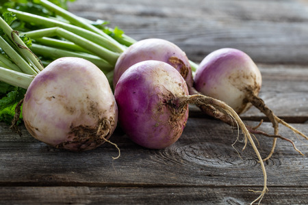 closeup of rustic organic turnips with fresh green tops and roots on old wood background for sustainable farming and vegetarian food, studio shot
