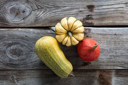 still life of different organic cucurbitaceae, kuri squash and green gourd for sustainable vegetable gardening over authentic old wood background, flat lay Stock Photo