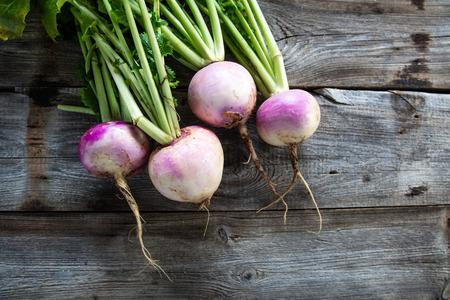 rustieke organische rapen met verse groene bovenkanten en wortels op echte houten achtergrond voor duurzame landbouw en vegetarisch voedsel, vlak leg Stockfoto