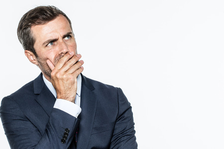 smart middle aged businessman thinking, looking up with hand hiding his mouth, expressing leadership reflections and concerns, copy space, white background studio Фото со стока