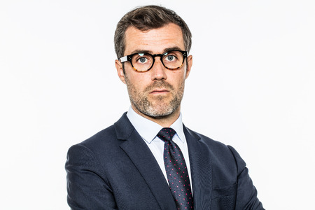 circumspect: daydreaming bearded middle aged businessman with eyeglasses thinking about and questioning corporate leadership, copy space, white background studio
