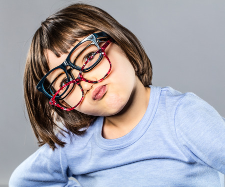 playful young child trying several eyeglasses on her nose, pouting, hesitating for the right choice, grey background studio
