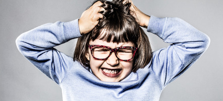 furious small kid having a tantrum, pulling out her hair for itchy allergies or scratching her head for anger and frustration, contrast effects