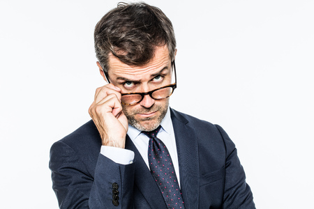dubious: dubious far-sighted middle aged businessman holding down his eyeglasses for reflection, looking concerned and questioning management, white background studio Stock Photo