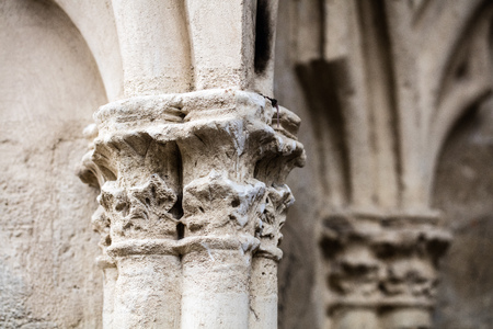 closeup of ancient limestone pillars damaged by pollution or ages made of carved stone