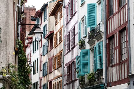 view of an old typical beautiful street with colorful timbers and wooden blinds for tourism in the South West of France in Europe Stock Photo