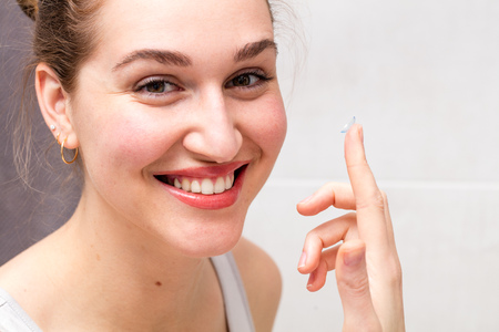 closeup portrait of a healthy young woman with a gorgeous smile holding a contact lens on her finger for farsighted, nearsighted or any optical eyesight solution from her bathroom