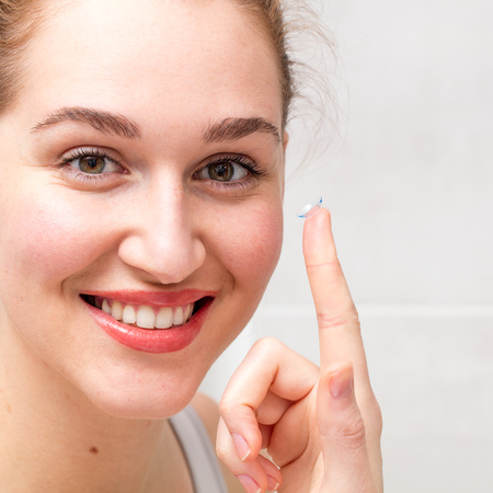 portrait of a smiling gorgeous young woman holding a contact lens on her finger for farsighted, nearsighted or any optical eyesight Stock Photo