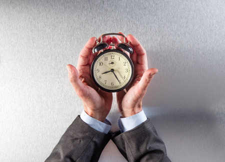 career timing: patient businessman hands holding an alarm clock for time management, business priority or multitasking concept on the workplace, flat lay view