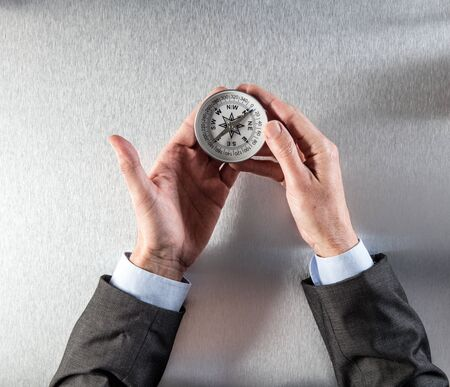 concept of corporate or career exploration for businessman hands holding a compass, showing a corporate direction for company vision, idea, management or perspective, above view