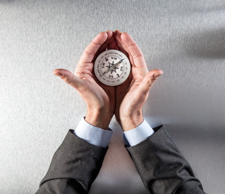 businessman hands displaying a compass in his palms for exploration symbol, finding the company perspective, vision, direction, management or idea forward, flat lay