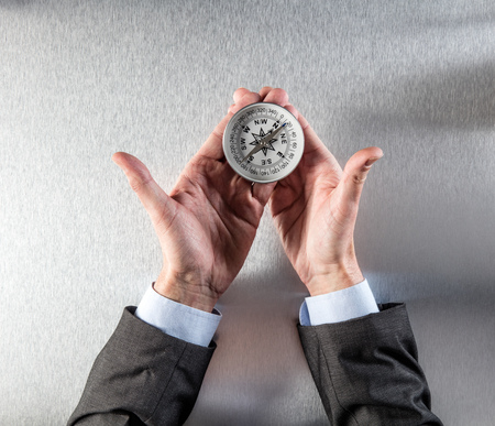 lay forward: concept of corporate exploration for businessman hands holding a compass, searching for a corporate direction, company vision, idea, management or perspective, above view Stock Photo