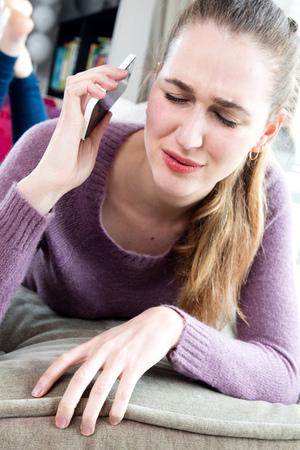 귀찮은 젊은 여자 고통에서 그녀의 휴대 전화를 들고 그녀의 귀를 멀리 그녀의 눈을 감 으면, 소파에 누워, 어려운 또는 슬픈 대화, 진짜 사람들이 직면