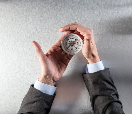 businessman hands holding a compass, searching for and managing the company direction, vision, orientation, management or career, flat lay