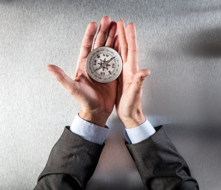 lay forward: businessman hands using a compass for exploration symbol, searching for the company direction, perspective, vision, management or idea forward, above view