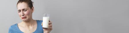 misselijk jonge vrouw weerzinwekkend bij het idee van het drinken van een glas stinkende melk of witte drank, lange kop met kopie ruimte Stockfoto