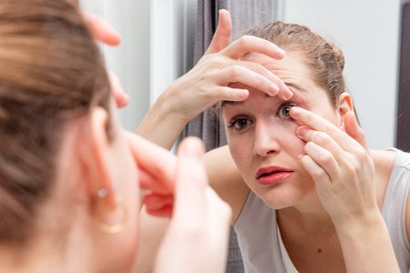 bathroom mirror: closeup of beautiful girl looking at herself leaning forward to bathroom mirror to apply or remove her contact lens, holding one eye lid, female face in a blurred foreground Stock Photo