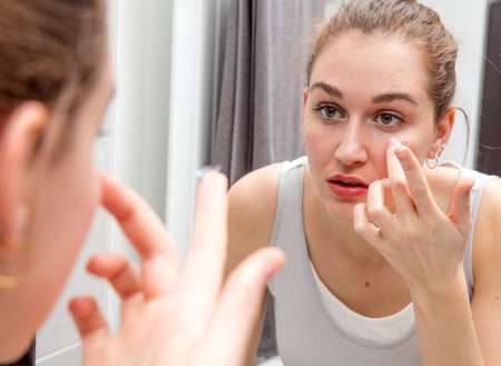 portrait of beautiful girl leaning forward to her home mirror to apply or remove her contact lens for morning routine, female face in a blurred foreground