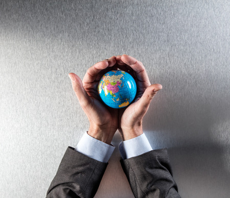 protecting businessman holding the earth within his hands for concept of human and corporate responsibility and international environment to care for, above view