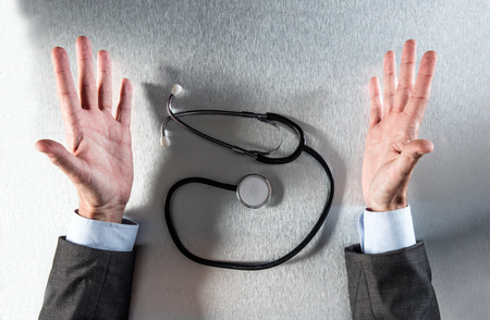 exasperated doctor hands with stethoscope on his medical desk talking about medicine, healthcare, health diagnosis or cardiology prevention, flat lay Stock Photo