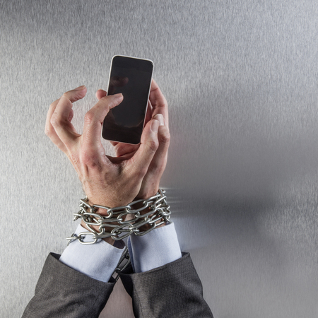 convicts: chain tied businessman hands typing on his mobile phone for concept of modern communication power and technology dependency, anonymous man, top view Stock Photo