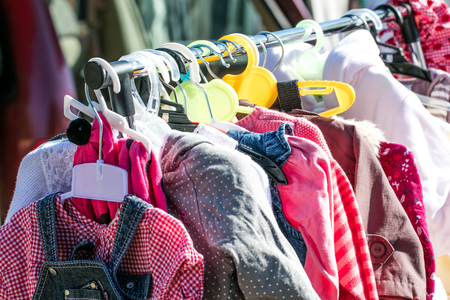 rack of beautiful second hand baby girl and children jackets and clothes displayed at outdoor garage sale for shopping, reusing, exchanging, recycling or donating
