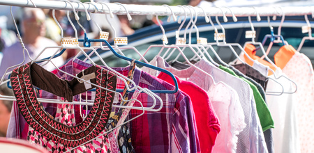 different pattern shirts and beautiful summer women fast fashion blouses display on rack at garage sale to resale, reuse or exchange outdoor Stock Photo