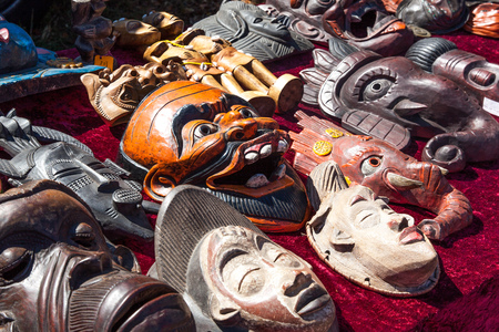 various wooden asian or african masks on sale for cultural or traditional collections at flea market