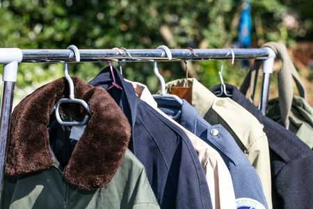 resale: women and men coats and jackets on rack display at garage sale or thrift store to resale, reuse, recycle or exchange outdoor