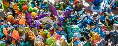 bulk of plastic miniature characters, monsters, dragons, knights and other small figurines sold at charity, garage sale or thrift store for childhood consumption, outdoors Stock Photo