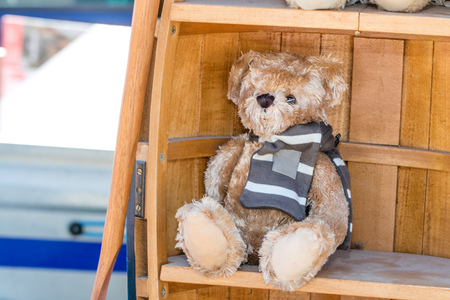 beautiful teddy bear with a winter scarf displayed in wooden library in boat shape for second hand child use at charity or boot sale outdoors Stock Photo