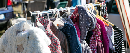 rack of second hand winter baby and children jackets and coats displayed at outdoor flea market for sale, exchange, recycle, donate and reuse against over-consumption shopping Stock Photo