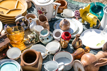 mix of household things and various dishes and toys at flea market for second hand, collection or over-consumption at outdoor charity Stock Photo