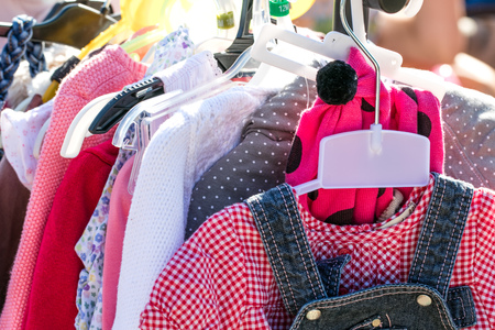close-up of beautiful second hand baby girl and child clothes displayed at outdoor garage sale for shopping, reusing, exchanging, recycling or donating