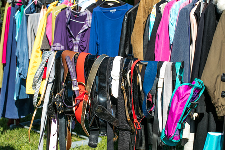 many belts and adult clothing on rack display at garage sale or thrift store to resale, reuse, recycle, exchange or donate outdoor Stock Photo