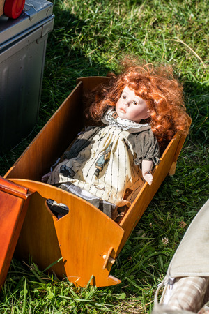 used red-hair doll with old fashioned clothes in wooden cradle on sale to be reused for collection, nostalgia or for another child to play with at flea market or charity sale, outdoor