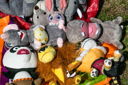 reselling baby and kid teddy bear toys displayed at garage sale of flea market for over-consumption society, outdoors