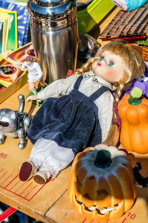 oldie: display of different second-hand doll, toys, decoration and football collectors on table at outdoor garage sale, flea market or street fair Stock Photo
