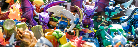 sold small: closeup of pile of plastic characters, dragons, knights, monsters and other small figurines sold at charity, flea market or thrift store for symbol of consumption and waste, outdoors Stock Photo