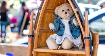 Schön angezogener Teddybär angezeigt in der hölzernen Bibliothek in der Bootsform für Nostalgie Gebrauch der zweiten Hand bei Nächstenliebe oder Stiefelverkauf draußen Standard-Bild - 83457654