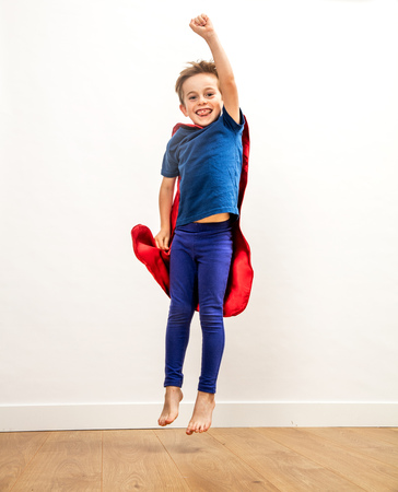 Laughing super hero boy jumping, flying with an excited arm raised, reaching happiness and victory over white background and wooden floor, indoor