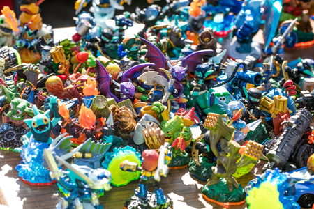 group of dragons, knights, monsters and other small plastic figurines sold at charity, flea market or thrift store for symbol of over-consumption and waste, outdoors