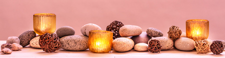 concept of pampering beauty, relaxing massage, pure spirituality, ayurveda or sensuality with mineral pebbles and warm candles, panoramic wallpaper
