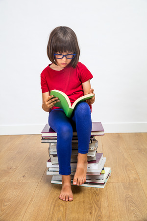 smart young primary schoolgirl with eyeglasses reading sitting on top of a stack of books for female power in studying and learning on white background, indoor
