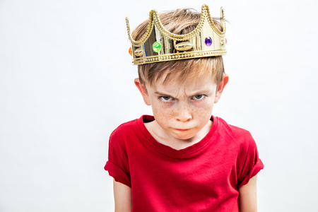 irritado muchacho estropeado hermoso con fruncir las pecas y una mirada sucia que llevaba una corona de oro para la actitud loca que mira la paternidad y la educación, fondo blanco, en el interior Foto de archivo