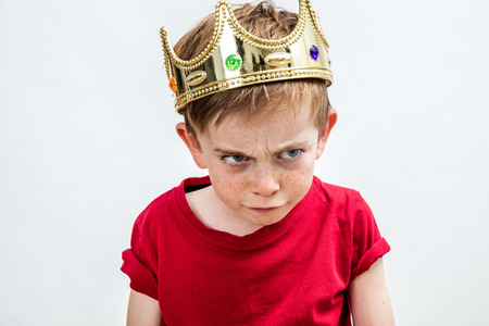 angry beautiful spoiled kid with frowning freckles wearing a king crown for mad attitude facing unhappy parenthood and education, white background, copy space