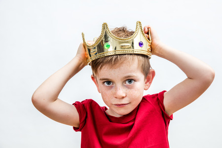 happy education and childhood concepts with an adorable 7-year old boy holding a golden king crown on his head as a wise spoiled child, white background Archivio Fotografico