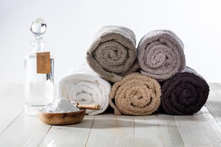 세련된 가정용 유연제가 포함 된 친환경적인 가정용 청소 및 지속 가능한 청소용 세탁물로 식초 및 나무 배경에 푹신한 말린 수건 베이킹 소다